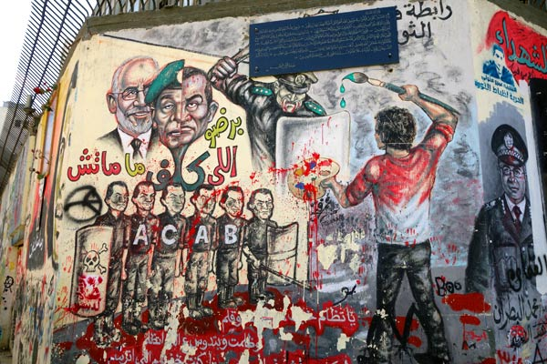 Colorful political art facing Tahrir Square celebrates the people's triumph, ridicules Mubarak, and warns of freedom's need for vigilance.