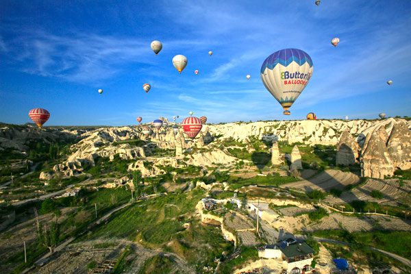 Every day through the season about a hundred balloons, each with a dozen or so passengers paying about $250 each, float for an hour across Cappadocia. Photo credit: Dean Cannon.