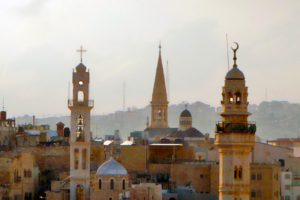 Bethlehem's skyline is decorated by silent steeples and singing minarets. The minarets crank up the volume and play five times a day.