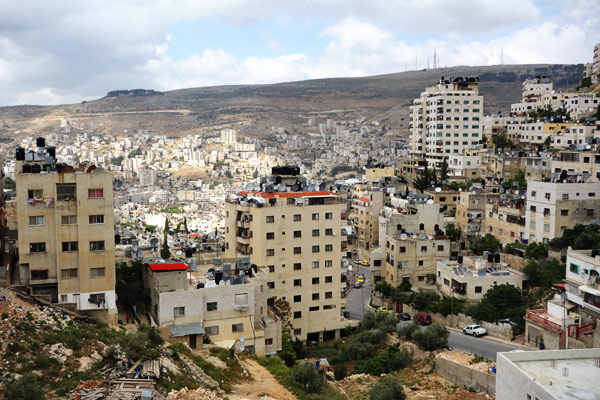 Like any Palestinian city, the skyline of Nablus is dotted with black water towers. Palestinian buildings can be identified by the gear on their roofs. While Israeli settlers have running water whenever they like, Israel controls and limits water service in the Palestinian Territories. Consequently Palestinians have black water tanks on their roofs and top them off whenever the water is running. Each community has its concerns: They say the first thing an Israeli considers when building a house is a bomb-hardened safe room, and the first thing a Palestinian considers is building a cistern. Along with solar panels, Palestinian rooftops also sport satellite disks to connect to Arab and international satellites, which serve as their window on the world.