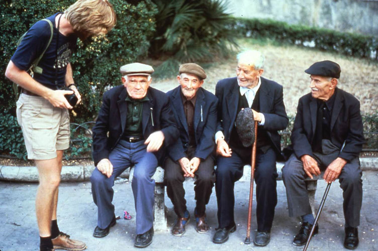"I've long used this photo to illustrate how good travel requires meeting people. ""If you see four cute guys sitting on a bench, ask them to scoot over."" I've been saying this for 30 years...and it still works. Find something...anything to talk about (like black socks and the joy of lots of pockets)."