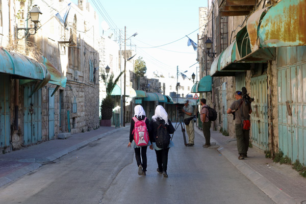 In the middle of all of Hebron's market activity is a pocket of tension and high security, surrounding the Tomb of Abraham. This ghost street, fronted by blocked-up buildings, divides the communities of the feuding descendants of Abraham.