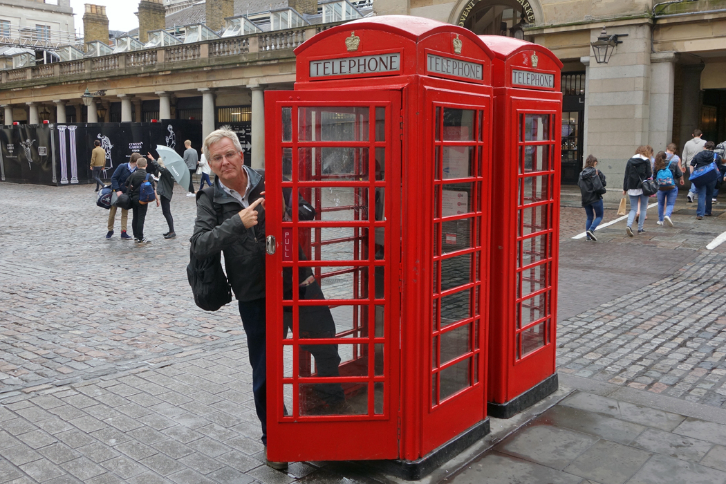 Rick Steves in a red phone booth in London, England