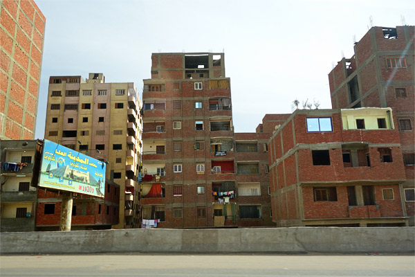 """Vast apartment blocks built without concern for code surround Cairo. Taking advantage of a loophole in the tax law, they are left technically """"unfinished"""" so their inhabitants pay no real estate tax. This way, the government gets no revenue, and the city looks uglier than ever. It's a two-fer!"""