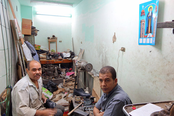 This Christian cobbler fixes Muslim shoes under Christian posters. Photo by Trish Feaster (for her Egypt blog, see http://thetravelphile.com)