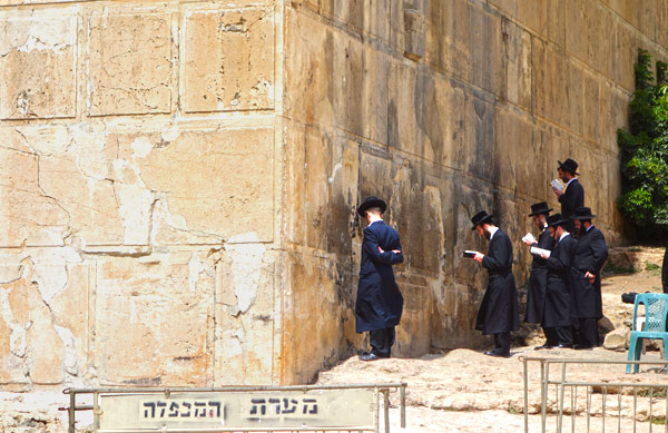 """Like they pray at the Western Wall of their destroyed temple in Jerusalem, Orthodox Jews pray at the foundation wall of their temple in Hebron. As at the Western Wall, the stones here are """"Herod Stones,"""" quarried and cut during the reign of King Herod and each with a distinctive carved border."""