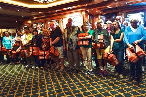 """Each cruise starts with the safety drill, with everyone reporting to their """"muster station."""" It's fun to see everyone decked out in life vests. While they explain how, in the event of an emergency, we'll all remain calm and walk to our assigned station, I can imagine pandemonium breaking out if there were a problem."""