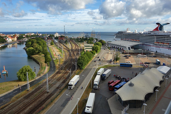 The cruise port of Warnemünde feels made-to-order for the arrival of cruise ships. Here you see the port, the terminal building (with exchange desk, tourist info, clichéd bars and eateries, and souvenir shops), buses gathering for various excursions, the train station (where private trains chartered by the cruise line await to whisk their cruise travelers south)...and the town itself, awaiting your business.
