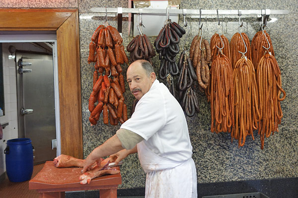 Sausage Man in Porto Old Industrial Age markets (like Bolhão in Porto) are busy with activity under 19th-century glass-and-steel rooftops. You can be on a diet, but your camera will eat this up — sausage man and all — with gusto.