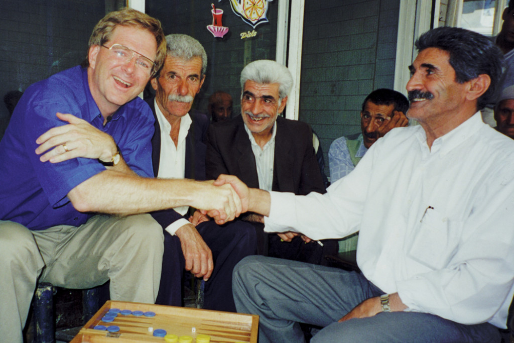 Rick Steves shaking hands with man in Istanbul while playing backgammon