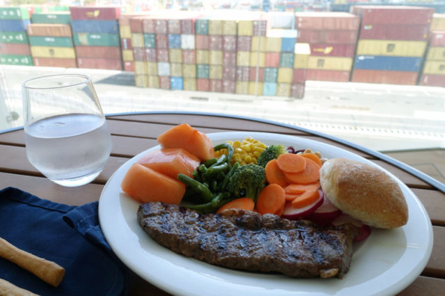 Eating on the cruise ship while at port with a view of shipping containers