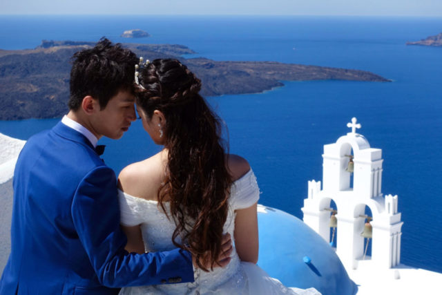 An engaged couple sweetly bumping heads looking out over Santorini