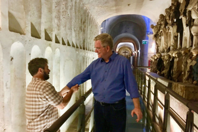 Simon Griffith rolling up Rick Steves' sleeve in capuchin crypt