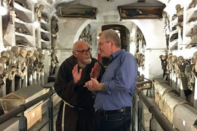 Rick Steves in Capuchin crypt with friar