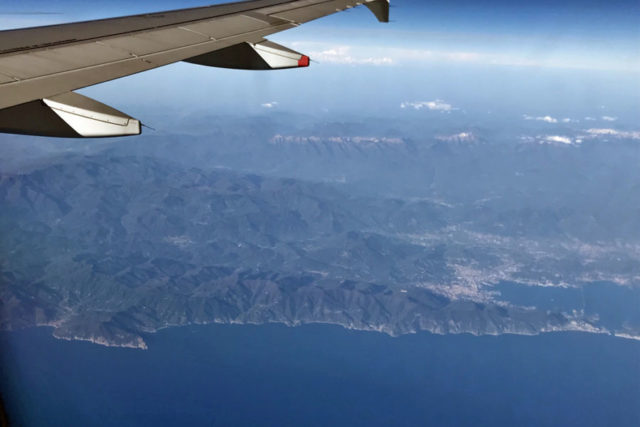 the coast of the Italian Riviera from above and plane wing in corner