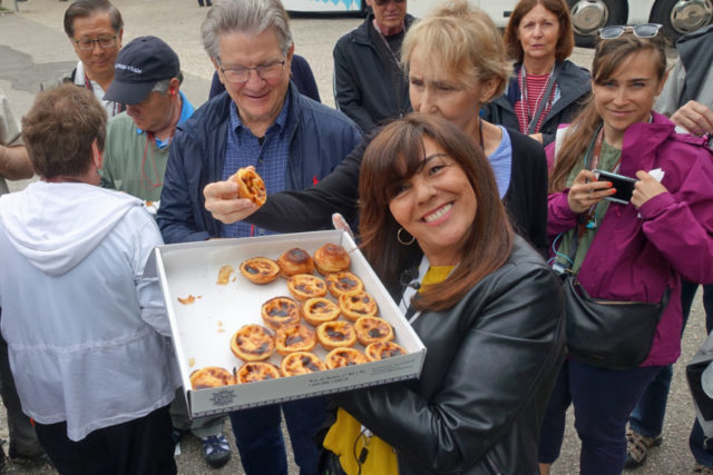 Fatima Bugarin smiling and holding a box of pasteis de belem, traditional Portuguese custard tarts