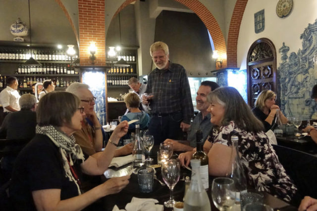Rick Steves Holding A Glass Of Wine And Standing Looking At Table Four