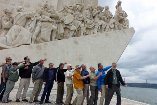 A line of men excitedly pointing forward, with Rick Steves at the front smiling and facing the camera, in front of a large stone monument that looks similar
