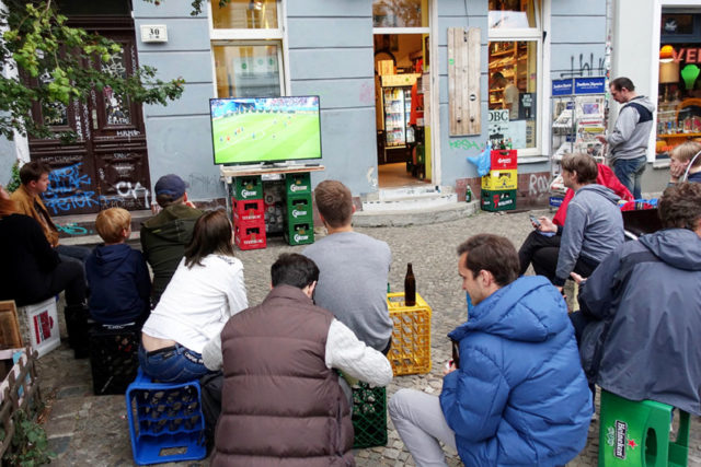 people sitting on crates outside a storefront in front of a small TV showing a soccer game