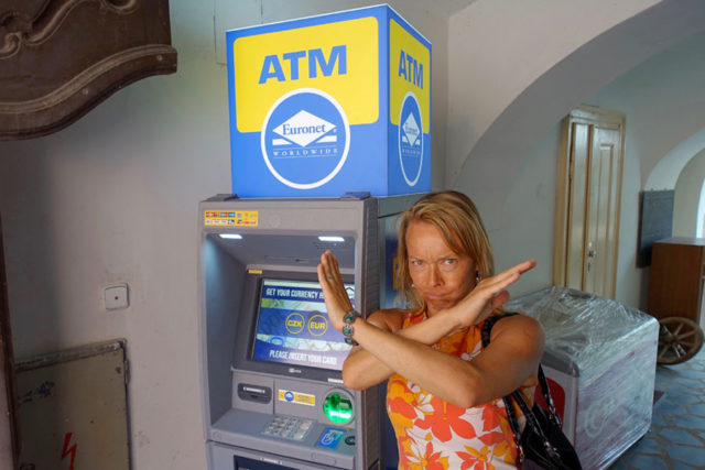 "guide holding an ""x"" in front of her face to mean ""bad"" next to ATM"