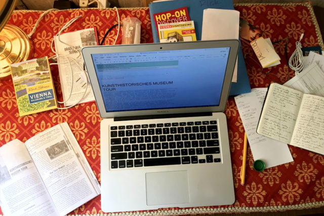 laptop strewn with guidebooks and notes
