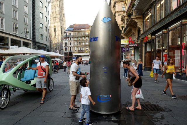 a large fountain shaped like a water bottle in vienna with people drinking from it