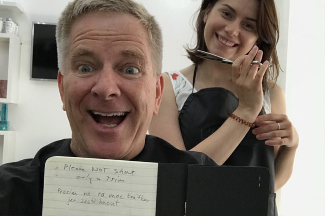 """rick steves and a stylist holding scissors. Rick is holding up a sign that says """"Please not short. Only a trim."""""""