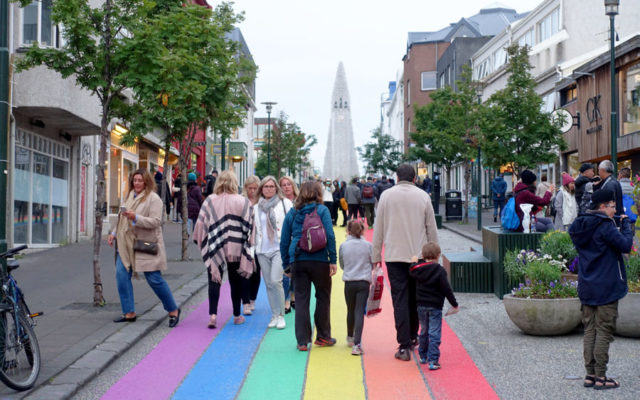 street in reykjavik painted with rainbow stripes and a view of Hallgrimskirkja Church in the distant background