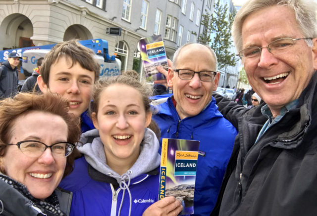 rick steves and a smiling family holding Rick Steves Iceland guidebooks