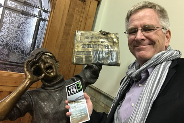 "rick steves holding a ""yes on 3"" pamphlet in front of a bronze statue that is of a newspaper boy who is hollering and holding a newspaper that has the word ""TRUTH"" written on it very largely"