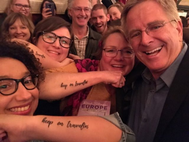 "rick steves selfie with three people who have ""keep on travelin"" tattooed on their arms"