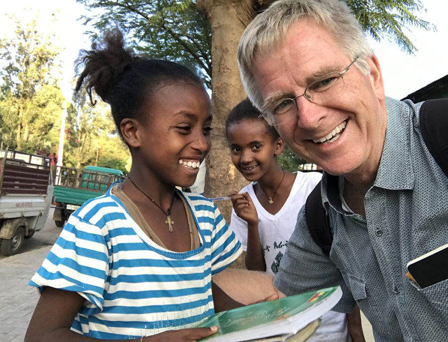 smiling rick steves with two school-aged girls who are laughing