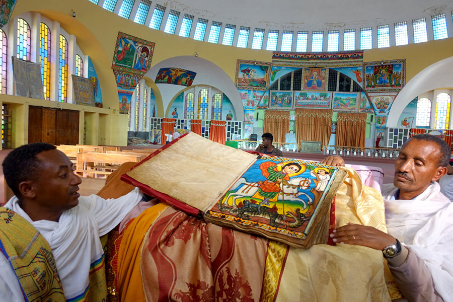 a large, old bible being held open to a page with a very colorful illustration