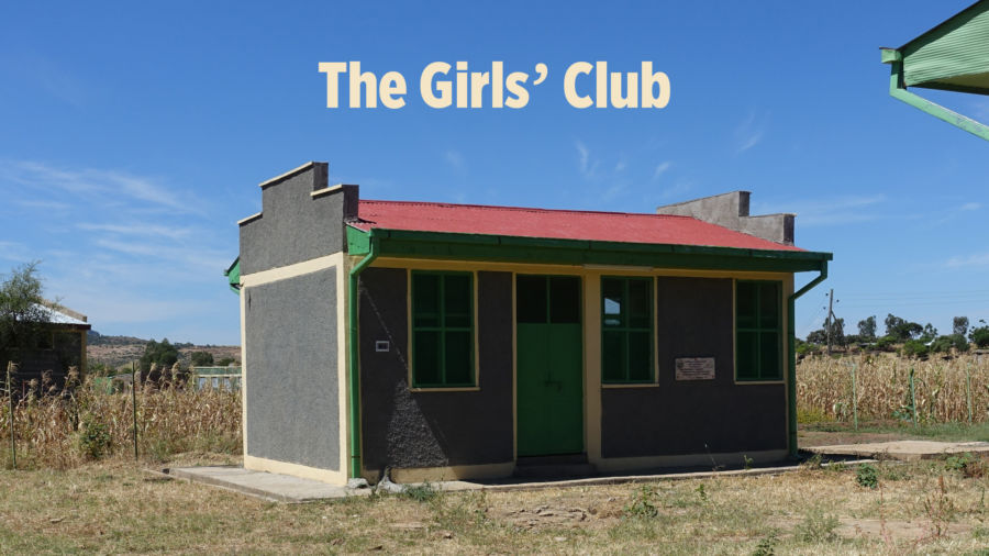 "a small colorful building with text above that says ""the girls' club"""