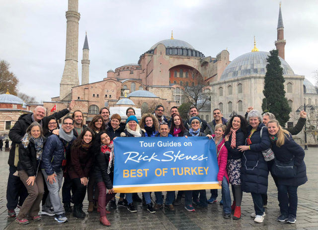 "group of tour guides in instanbul holding up a sign that says ""Tour Guides on Rick Steves Best of Turkey"""