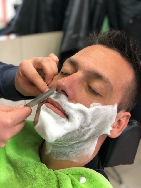 man with shaving cream on his face getting a shave