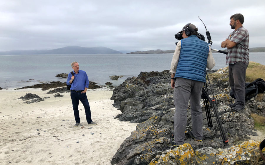rick steves standing on a white sand beach while his tv crew are huddled over a camera that's pointing at him