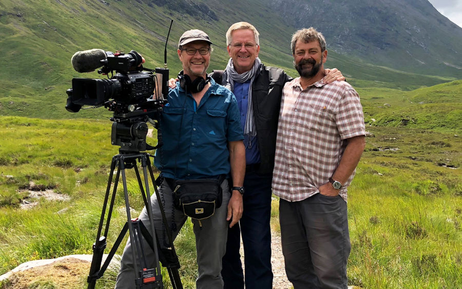 rick steves with his arms around karel bauer and simon griffith and karel is holding a large camera. the three are standing in a green field