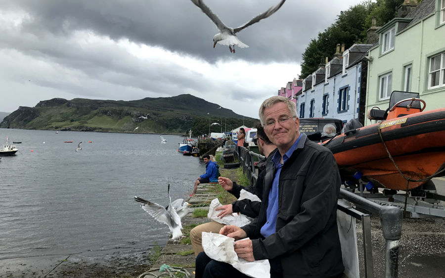 rick steves sitting on a beach overlooking the sea with food in his lap and a seagull is overhead very near to him