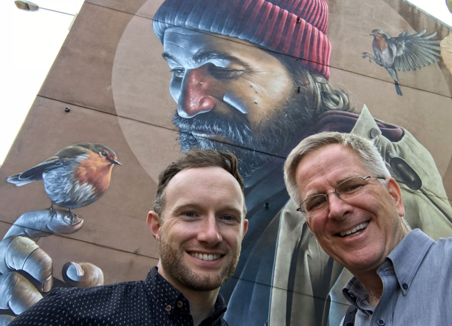 rick steves and tour guide colin mairs similing in front of a wall with street art